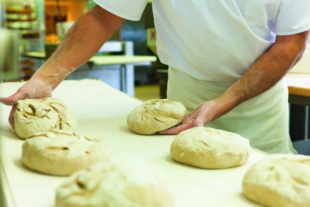 Male baker baking fresh bread in the bakehouse